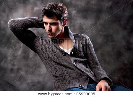 Hübsche junge Mann posiert auf dunklem Hintergrund