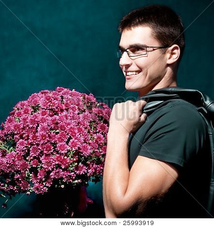 Close up romantic man with glasses holding big bouquet of flowers to woman for Valentine's Day.