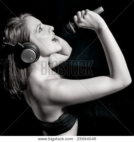 Black and white portrait of beautiful  woman with headphones and mic, studio shot