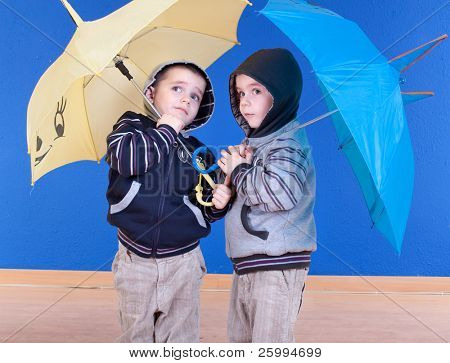 Twins brother  have fun under an umbrellas, studio shot