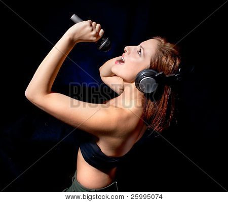 Beautiful  woman with headphones and mic singing her favorite song