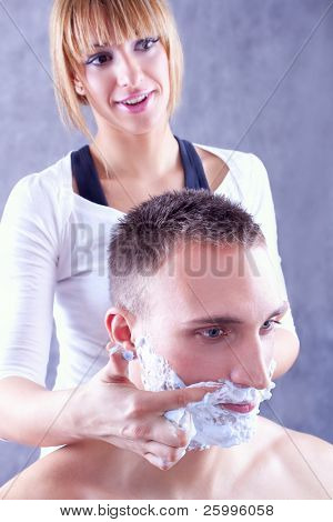 Young woman applying shaving cream on male face , studio shot