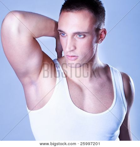 A trendy European man dressed in undershirt. Studio shot