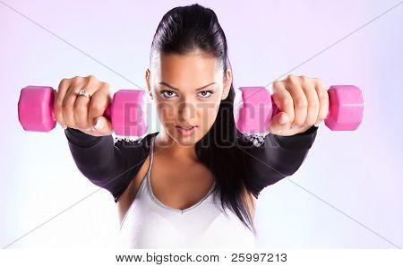 Young woman hang up hands weights ,studio shot