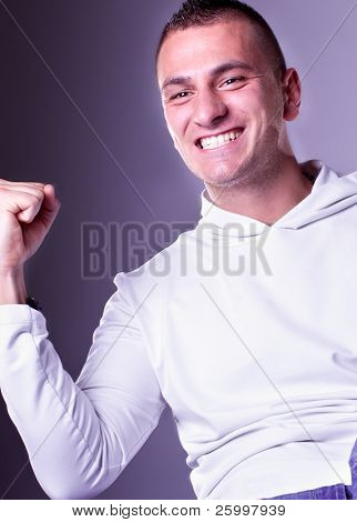 Champion man standing with fists clenched in victory.Close up studio shot