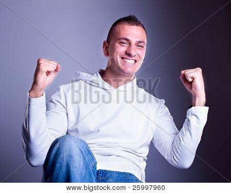 Mann, stehend mit Fäuste ballte Sieg Sieger. Studioaufnahme
