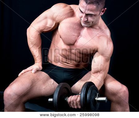 Man on bench with a bar weights in hands training, isolated on black
