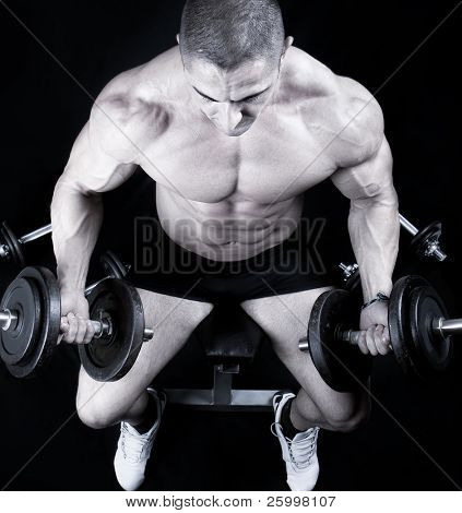 Man on bench with a bar weights in hands training,black and white shot