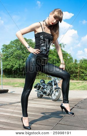 A pretty woman near by motorcycle  posing