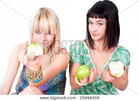 Two young women  offer a green apples. Close up .