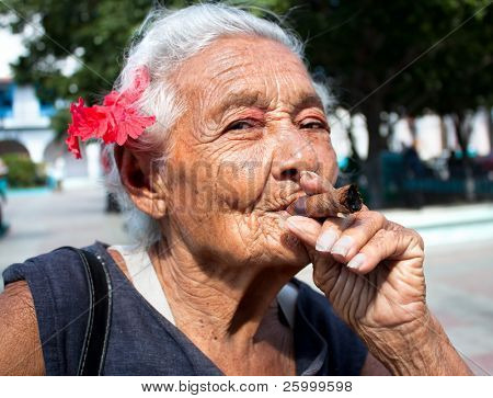 Old wrinkled woman with red flower smoking cigar. Santiago de Cuba, Cuba