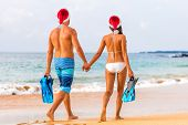 Christmas beach couple caribbean winter holiday couple wearing santa hats on exotic vacation. Young  poster