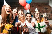 Group Of Friends Holding Gifts, Sparklers And Raising Glasses With Champagne, Multicultural Bearded  poster