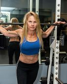 Serious Female Weight Lifted Showing Strong Abdominal Muscles While Posed In Gym Squat Rack. poster