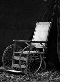 stock photo of antique wheelchair  - an antique wheelchair in black and white - JPG