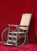 picture of antique wheelchair  - an antique wheelchair seen against red velvet - JPG