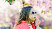 Tenderness Concept. Girl On Dreamy Face Standing In Front Of Sakura Flowers, Defocused. Girl With Lo poster