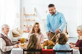Big Family Having Delicious Thanksgiving Dinner Together At Home While Father Cutting Turkey poster