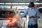 Young Asian Auto Mechanic Holding Digital Tablet Checking Tail Light In Auto Service Garage. Mechani poster