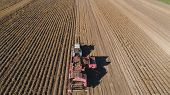 Potatoes Harvesting Machine With Tractor In Farm Land For Harvesting Potatoes. Farm Machinery Harves poster