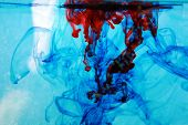 stock photo of early 60s  - red and blue food coloring floats freely in a tank of clean clear water in a psychedelic pattern that is reminiscent of the early 1970 - JPG