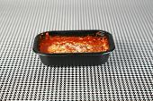 picture of frozen tv dinner  - Hot fresh from the Microwave oven a Lasagna tv dinner sits on a black and white background waiting to be eaten by a hungry person about to watch their favorite tv program - JPG