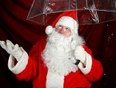 image of 24th  - Santa Claus holds his transparent umbrella and checks for signs of snow before he goes to work on December 24th Christmas Eve - JPG