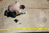picture of blood drive  - a crime scene detective investigates and gathers evidence at a drive by shooting crime scene - JPG