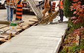 pic of concrete pouring  - Cement mixer pouring cement for new sidewalk - JPG