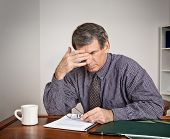 picture of mature men  - Tired stressed out businessman rubs his eyes while seated at a desk reading reports - JPG