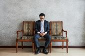 Serious Focused Asian Man In Formal Suit Sitting On Chair Looking Down In Deep Thoughts poster
