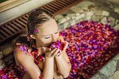 Attractive Young Woman In Bath With Petals Of Tropical Flowers And Aroma Oils. Spa Treatments For Sk poster