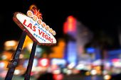 Famous Las Vegas sign at night with Las Vegas Cityscape blur background. poster