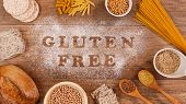 Gluten Free Products Gathering Around Words Written In Special Flour On The Table - Top View poster