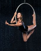 Young Beautiful Slim Circus Artist On Aerial Hoop Posing On A Black Aqua Studio Background poster