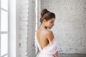 Attractive Tender Young Woman With Hair Bun Standing In Spacious Room Wearing Pink Ball Dress, Demon poster