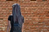 A Girl With Hair Braided In Braids Stands With Her Back And Looks At The Brick Wall. poster
