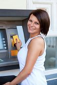 stock photo of automatic teller machine  - Woman withdrawing money from credit card at ATM - JPG
