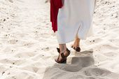 Cropped Image Of Jesus In Robe, Sandals And Red Sash Walking On Sand In Desert poster