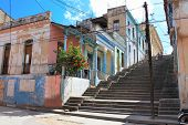 Long Padre Pico staps with crumbling buildings in Santiago de Cuba , Cuba