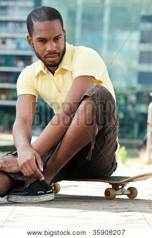 Young Male Sitting On Skateboard and Looking at the Camera