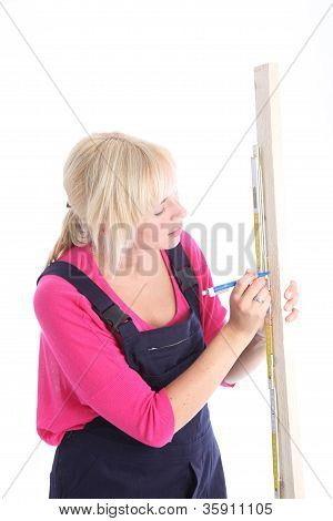 Woman Measuring A Length Of Wood