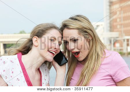 Two Ladies Listening To A Mobile Phone