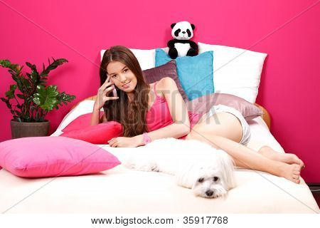 Nice Teenager Making A Phone Call In Her Room With Her Little White Dog