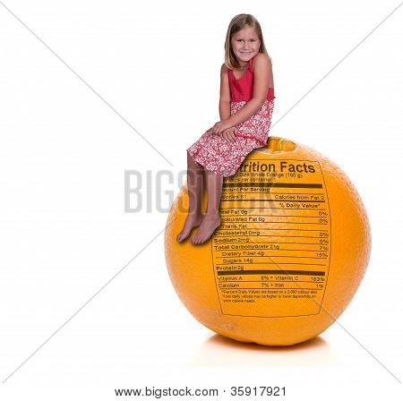 Girl Sitting On Orange With Nutrition Label