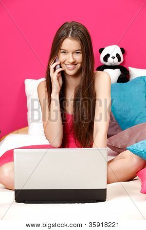 Cute Girl Smiling And Making A Call In Her Pink Room