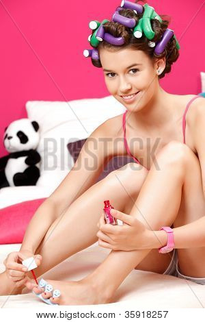 Portrait Of A Young Natural Woman, Painting Her Toenails With Red Nail Polish