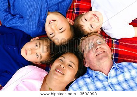 Family Of Five On Red Garden Rug Lying Outdoors