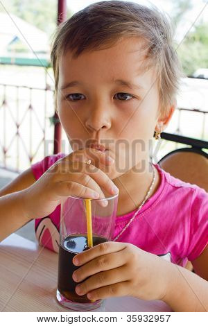 A Little Girl Drinking Juice At The Cafe