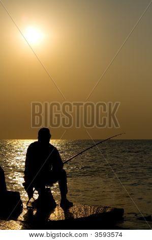 Fisherman Silhouette At Sea Sunset
